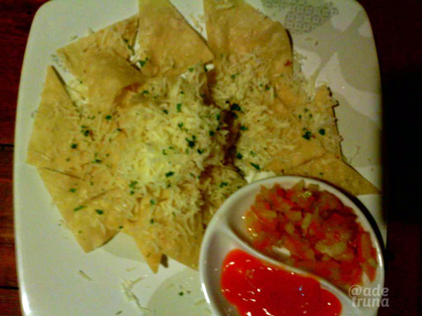 Nachos itu Tortilla renyah kriuk-kriuk ditaburi keju dengan saus irisan tomat dan bawang.